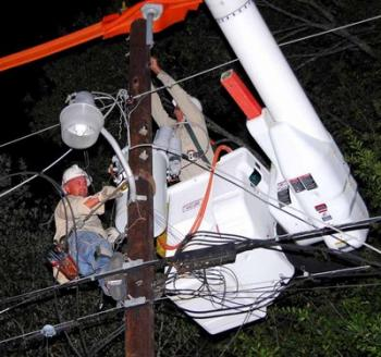 With a safety belt and climbers, SLEMCO lineman Byron Branch of Breaux Bridge (left) clings to a light pole just off Hebert Lane Highway near Parks while Dale Taylor of Carencro works out of a cherrypicker's bucket.<!--break--> The Lafayette District linemen changed out a blown transformer Sunday night.